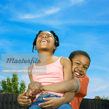 Brother Lifting His Sister as They Play Together Outside Stock Photo - Premium Royalty-Free, Image code: 6106-07004056