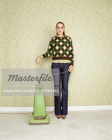 Portrait of a Woman Standing Next to a Vacuum Cleaner, Against a Wall Decorated with Green Wallpaper Stock Photo - Premium Royalty-Free, Image code: 6106-07005343