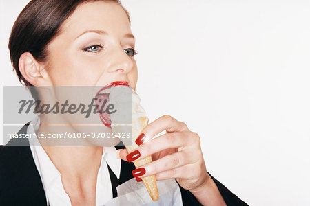 Businesswoman Eating an Ice Cream Stock Photo - Premium Royalty-Free, Image code: 6106-07005429
