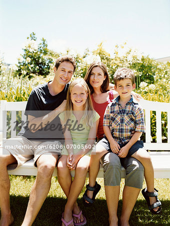 Family of Four Sit Together on a Park Bench in Sunlight Stock Photo - Premium Royalty-Free, Image code: 6106-07005602