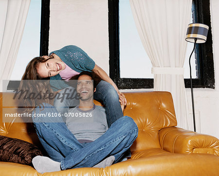 Couple Mucking About Together and Laughing on a Leather Sofa Stock Photo - Premium Royalty-Free, Image code: 6106-07005826