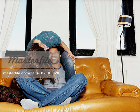 Couple Mucking About Together on a Leather Sofa Stock Photo - Premium Royalty-Free, Image code: 6106-07005828