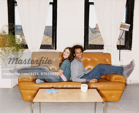 Portrait of a Couple Sitting Back to Back on a Leather Sofa Stock Photo - Premium Royalty-Free, Image code: 6106-07005830