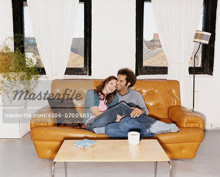 Couple Sat Together on a Leather Sofa Stock Photo - Premium Royalty-Free, Image code: 6106-07005831