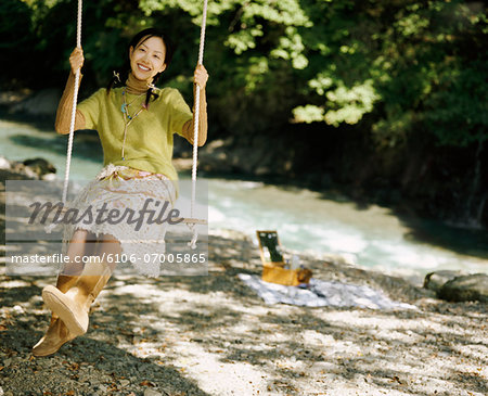 Young Woman Swinging on a Rope Swing Stock Photo - Premium Royalty-Free, Image code: 6106-07005865