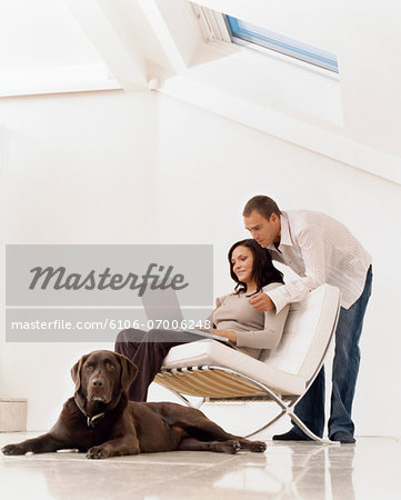 Woman Using a Laptop Computer with a Man Standing Behind her and a Pet Dog Sitting on the Floor Stock Photo - Premium Royalty-Free, Image code: 6106-07006248