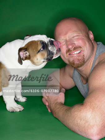 Muscular Man Being Licked by a Bulldog Stock Photo - Premium Royalty-Free, Image code: 6106-07007380