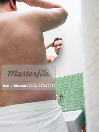 Rear View of an Overweight Man Wrapped in a Towel, Looking at a Bathroom Mirror Stock Photo - Premium Royalty-Free, Image code: 6106-07009259