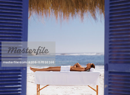 Naked Woman Lies on a Bench on the Beach, Covered With a Towel, Sunbathing Stock Photo - Premium Royalty-Free, Image code: 6106-07010166