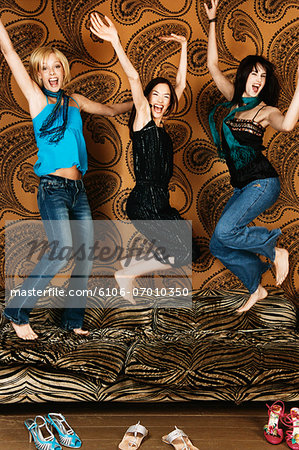 Three Young Women Jumping on a Sofa Stock Photo - Premium Royalty-Free, Image code: 6106-07010350