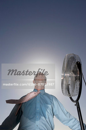 Low Angle View of a Sweaty Businessman Standing Next to an Electric Fan Stock Photo - Premium Royalty-Free, Image code: 6106-07010987