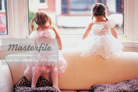 Two Girls in Fancy Dress Looking out of a Window Stock Photo - Premium Royalty-Free, Image code: 6106-07016751