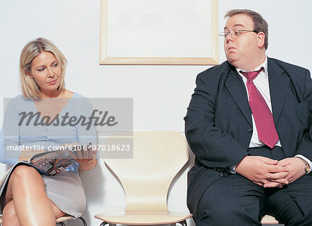 Overweight Businessman Looking at Woman's Magazine In Doctor's Office Stock Photo - Premium Royalty-Free, Image code: 6106-07018623