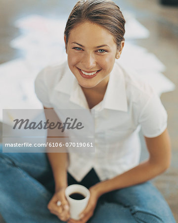 Businesswoman Sitting Cross Legged by Some Documents With a Cup of Coffee Stock Photo - Premium Royalty-Free, Image code: 6106-07019061