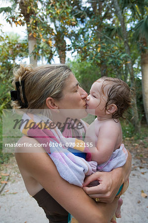 Mother kissing baby daughter (9-12 months) on beach, profile Stock Photo - Premium Royalty-Free, Image code: 6106-07022155