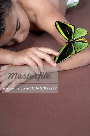 Boy (4-5) lying down and looking at large green butterfly on arm Stock Photo - Premium Royalty-Free, Image code: 6106-07022227
