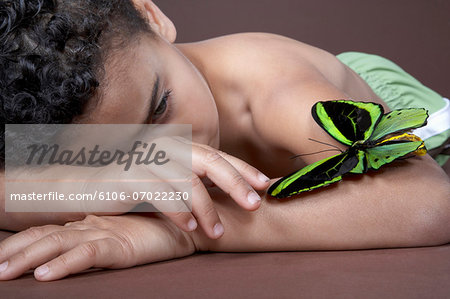 Boy (4-5) lying down and looking at large green butterfly on arm, close-up Stock Photo - Premium Royalty-Free, Image code: 6106-07022230