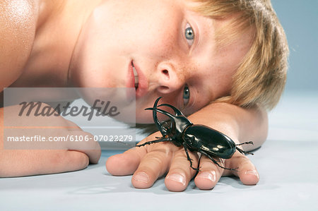 Boy (10-11) looking at large black beetle crawling on hand, close-up Stock Photo - Premium Royalty-Free, Image code: 6106-07022279