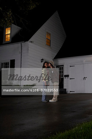 Boy (12-13) kissing girl (12-13), girl turning head, in driveway in front of house, side view, night Stock Photo - Premium Royalty-Free, Image code: 6106-07022553