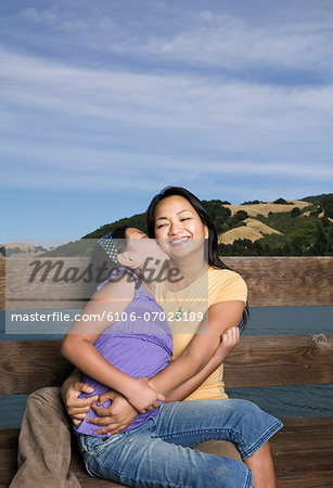 Mother and daughter (10-11 years) sitting by wooden balustrade Stock Photo - Premium Royalty-Free, Image code: 6106-07023189