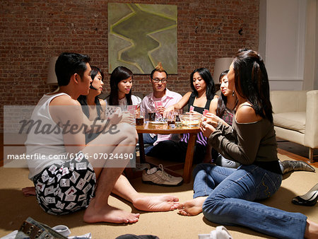 Group of friends sitting on floor around table in living room playing strip poker Stock Photo - Premium Royalty-Free, Image code: 6106-07024490