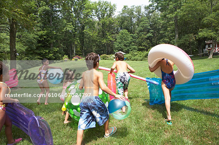 Group of children (5-10) running up hill towards pool with pool floats, rear view Stock Photo - Premium Royalty-Free, Image code: 6106-07024797