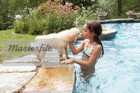 Girl (8-9) in swimming pool, kissing dog, side view Stock Photo - Premium Royalty-Free, Image code: 6106-07024802