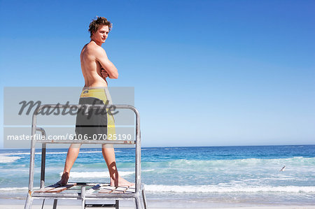 Young man standing on lifeguard podium, rear view Stock Photo - Premium Royalty-Free, Image code: 6106-07025190