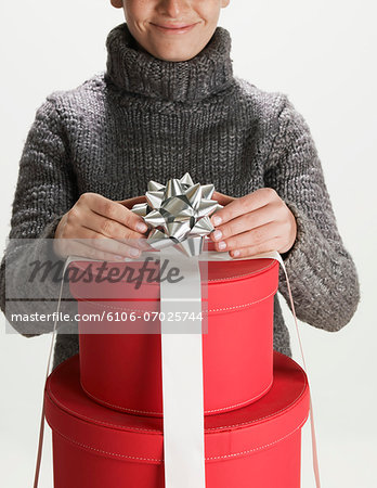Young woman tying bow on stack of gift boxes Stock Photo - Premium Royalty-Free, Image code: 6106-07025744