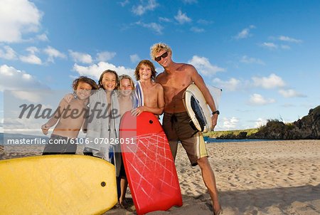 Man and four boys (8-13) with body boards and surfboard, on beach,  portrait Stock Photo - Premium Royalty-Free, Image code: 6106-07026051