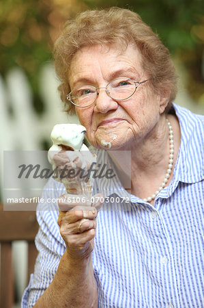 Old lady with ice cream smiling Stock Photo - Premium Royalty-Free, Image code: 6106-07030072
