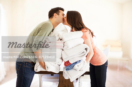 Couple doing laundry Stock Photo - Premium Royalty-Free, Image code: 6106-07120410