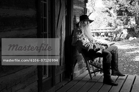 Old cowboy with a gun on a chair Stock Photo - Premium Royalty-Free, Image code: 6106-07120994