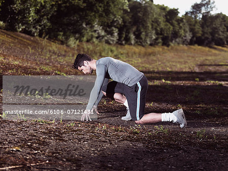 athlete in sprinting position Stock Photo - Premium Royalty-Free, Image code: 6106-07121431