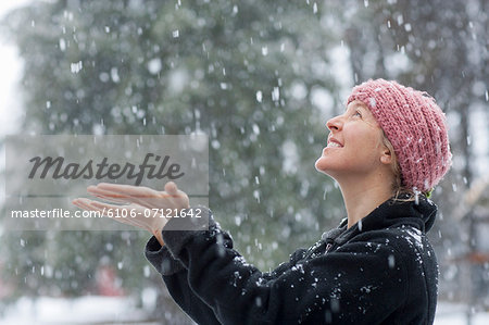 Woman excited to see snowfall in winter Stock Photo - Premium Royalty-Free, Image code: 6106-07121642