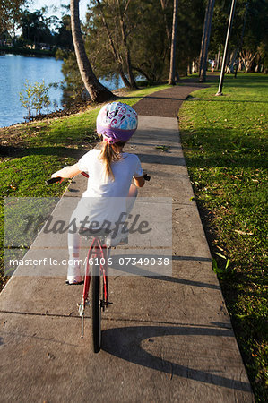 Young Girl Learning to Ride Bicycle Stock Photo - Premium Royalty-Free, Image code: 6106-07349038