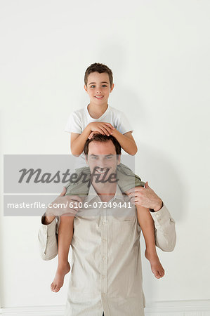 Happy Father Carrying His Son On Shoulder Stock Photo - Premium Royalty-Free, Image code: 6106-07349441