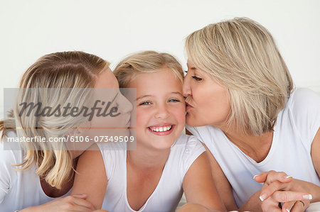 Mother And Grandmother Kissing Girl Stock Photo - Premium Royalty-Free, Image code: 6106-07349509