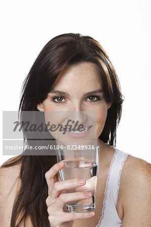 Close up of smiling woman holding glass of water Stock Photo - Premium Royalty-Free, Image code: 6106-07349936