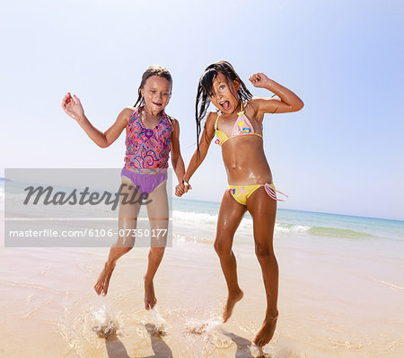 Two young girls jumping on the beach Stock Photo - Premium Royalty-Free, Image code: 6106-07350177