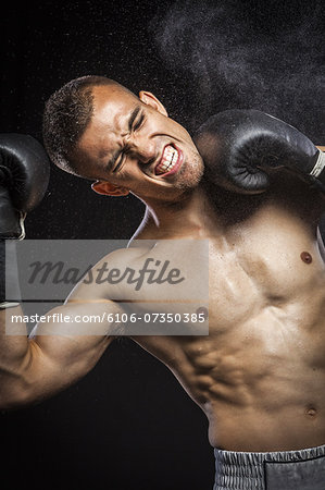Male boxer getting punch in face. Stock Photo - Premium Royalty-Free, Image code: 6106-07350385
