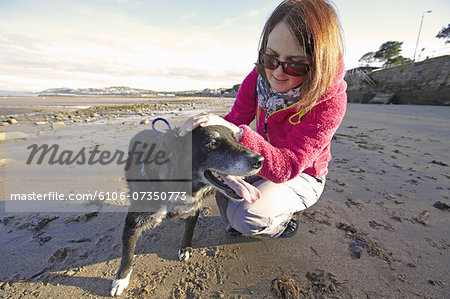 woman training dog on sandy beach Stock Photo - Premium Royalty-Free, Image code: 6106-07350773