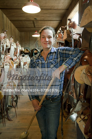 Woman with broom in horse tack room. Stock Photo - Premium Royalty-Free, Image code: 6106-07350970