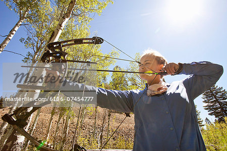Woman shooting compound bow at target in woods. Stock Photo - Premium Royalty-Free, Image code: 6106-07454777