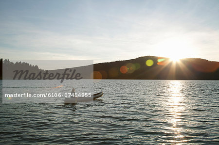 Woman paddling canoe at sunset on lake. Stock Photo - Premium Royalty-Free, Image code: 6106-07454955