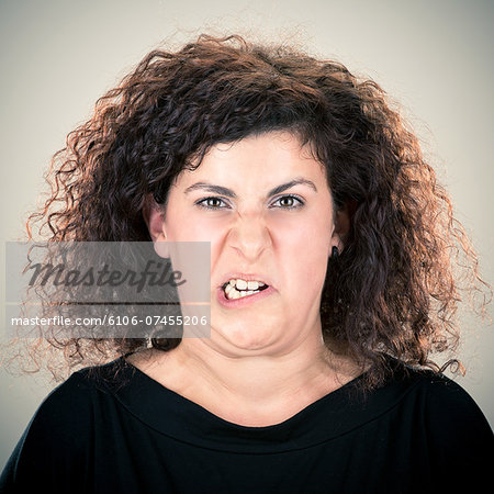 Young long curly hair lady grimacing portrait Stock Photo - Premium Royalty-Free, Image code: 6106-07455206