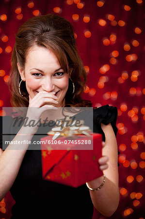 Christmas: Giggling Woman Offers Present Stock Photo - Premium Royalty-Free, Image code: 6106-07455288