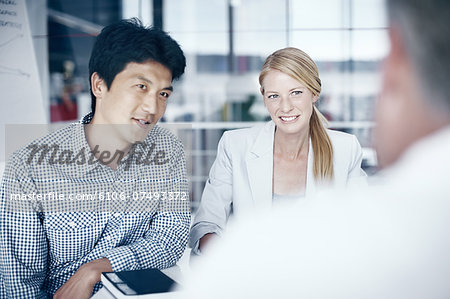 Three colleagues in a meeting Stock Photo - Premium Royalty-Free, Image code: 6106-07493372
