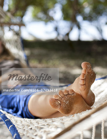 A woman relaxes in a hammock on the beach. Stock Photo - Premium Royalty-Free, Image code: 6106-07493618