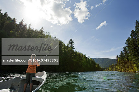 Woman fly fishing from drift boat on river. Stock Photo - Premium Royalty-Free, Image code: 6106-07493801